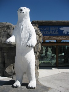 A huge white polar bear sculpture stands in front of the polar bear exhibit.