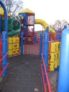 "The ""small"" piece of playground equipment. This view shoes slides and two of the 'games' from a ramp onto the equipment."