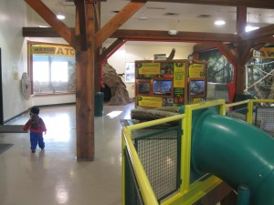 Peanut toddles across the top floor of the discovery barn.  There's the top of a 2-story slide in the foreground; the frog ark and meerkats are to the top of the photo.