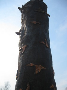A carved tree by the pond at the cemetery; it has 3D images of birds in flight.