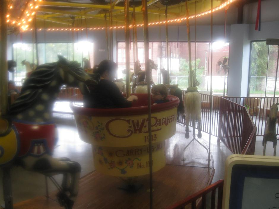 The left majority of the photo is the 1913 carousel; Peanut and Phouka are in a cup-like seat in the center of the photo. There's a glimpse of the hand-crank carousel to the right of the photo.