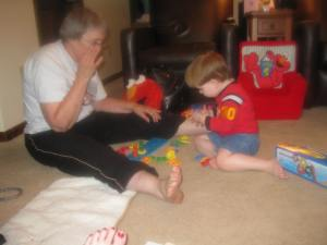 Grandma and Peanut play with the shape sorter at my parents' house. There are chairs and Elmos in the background.