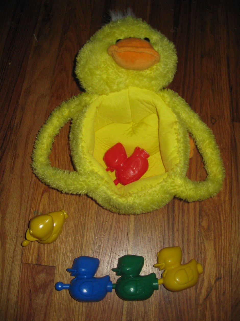 A bright yellow plush basket made to look like a duckling is at the top of the photo; a bright red duck-shaped pop bead is lying on its side in the basket. Beneath the basket to the left is a yellow duck-shaped bead sitting upright. At the bottom of the photo, blue, green and yellow duck-shaped pop beads are attached in a row.
