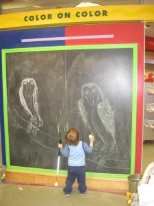 Photograph of the giant chalk board.  There's an owl that's been drawn on each side of the board by little girls who were there before us, and Peanut's standing in front of the chalkboard.  The chalkboard's about 3 times his height.