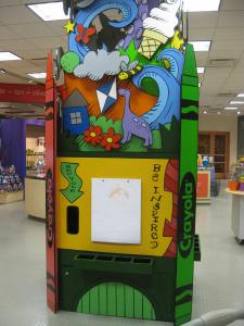 """A large, square column features """"easels"""" with drawing paper for children."""