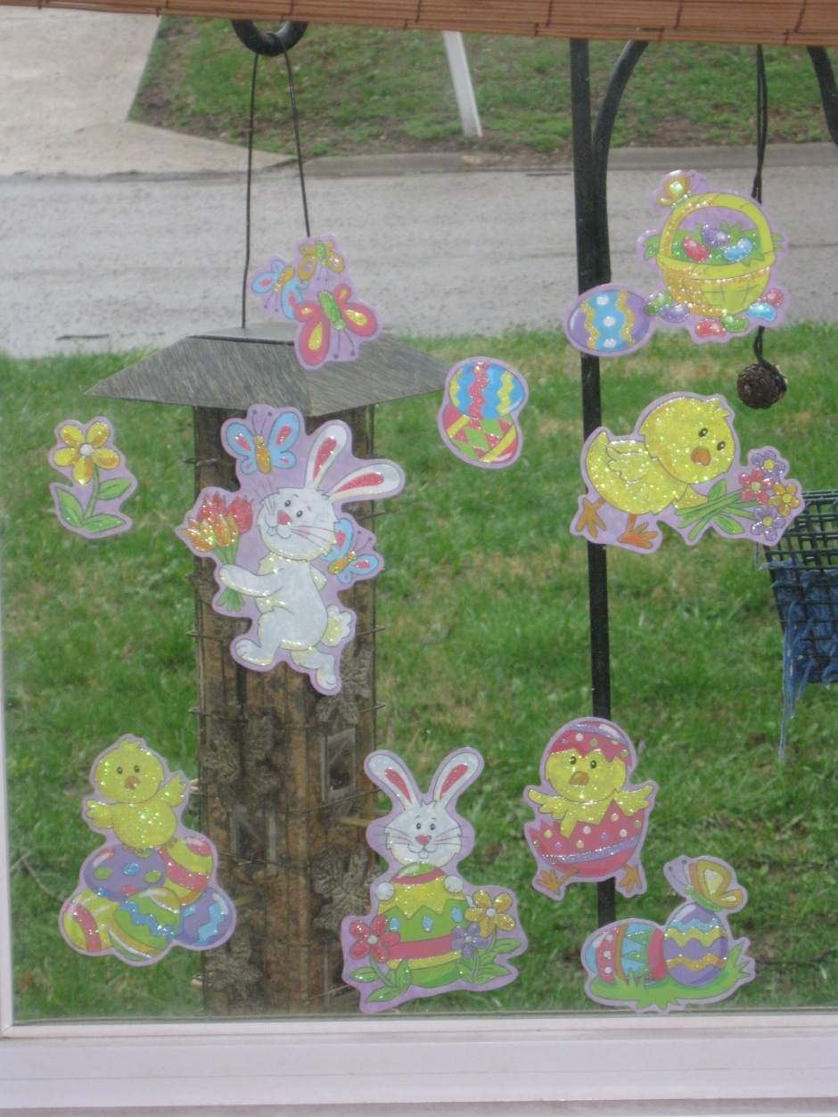 The Easter window clings on our front window. A birdfeeder, our front yard and the street are in the background.
