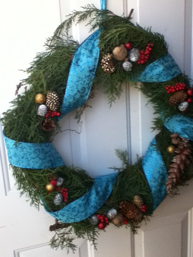 Green juniper wreath on our front door, wrapped with blue ribbon and with pinecones, etc. on it.