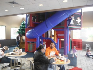 A couple sits at a table in front of a four-story indoor play area.