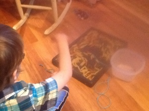 At the left corner of the screen, a small boy sits with his right arm raised. His back is to you.  At the right side of the photo is a black tray filled with multi-colored pasta.