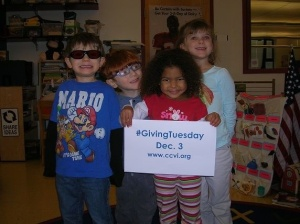 A group of four children hold a sign promoting giving Tuesday at CCVI