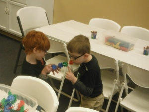 Peanut and a friend work with the circular construction toys.
