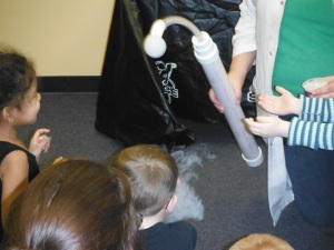 The tube holds dry ice, water, and a bit of baby soap.  The bubbles were huge, white, and poofed into vapor shortly after touching your hands (or feet--feet were a popular choice on Saturday!).