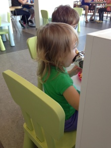 Sprout and Peanut sit at one of the child-sized tables in the IKEA cafeteria.