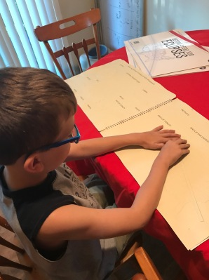 Photo of young boy reading a braille copy of Getting a Feel for Eclipses.